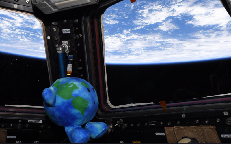 Earth plush toy looks out of ISS Cupola observatory module.
